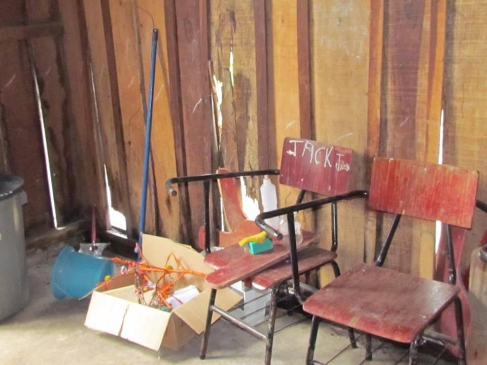 Das poucas cadeiras do barracão-escola, a maioria está quebrada