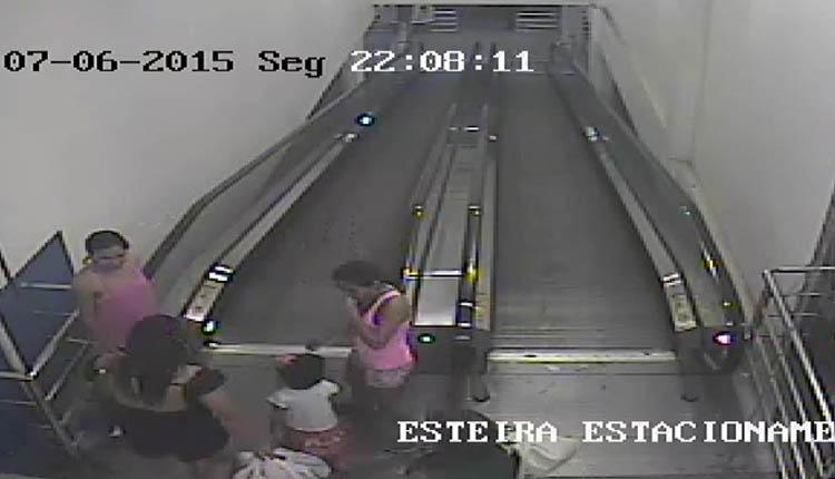 Criança desce na esteira rotativa, na loja, observada por clientes