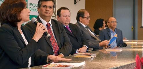 Governador Flávio Dino lança o Escola Digna. Na mesa e mãos do coronel Humberto Coutinho, a cartilha do programa feita por uma subcontratada pela Pública